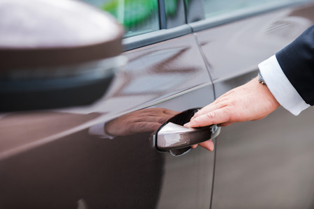 handcarves: Hand on handle. Close-up of man in formalwear opening vehicle door