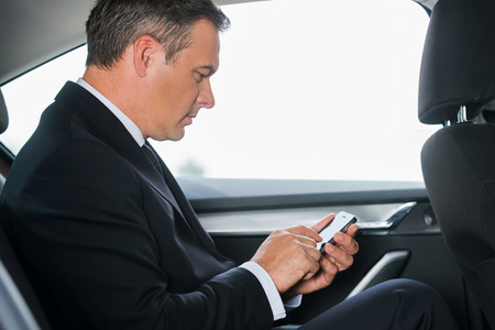 text message: Sending an urgent message. Side view of confident mature businessman typing message on his smart phone while sitting on the back seat of a car  Stock Photo