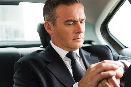 looking at watch: I will be in time. Confident mature businessman looking at his watch while sitting on the back seat of a car  Stock Photo
