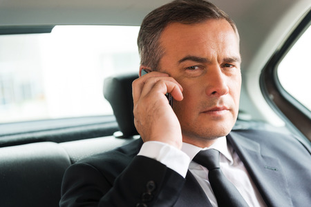senior business man: Successful businessman in car. Confident mature businessman talking on the mobile phone and looking away while sitting on the back seat of a car