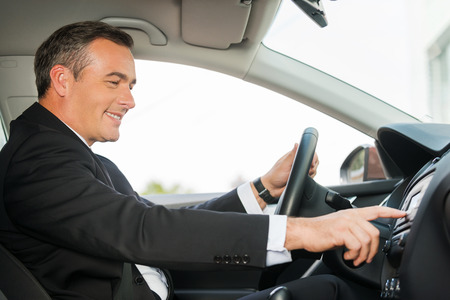 car safety: Driving with comfort. Side view of cheerful mature man in formalwear driving car and touching dashboard with finger