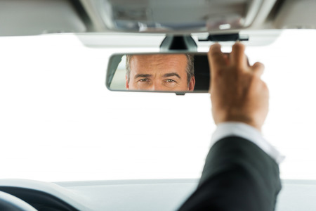 new motor car: Man adjusting car mirror. Close-up of mature man in formalwear adjusting mirror while sitting in his car