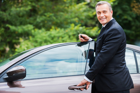 door man: This car is perfect for me. Cheerful mature man in formalwear looking at camera and smiling while standing near his new car