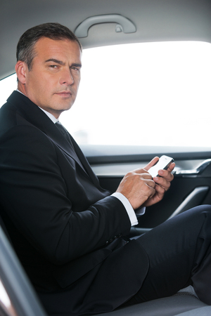 Typing a business message. Side view of confident mature businessman typing message on his smart phone and looking at camera while sitting on the back seat of a car  photo