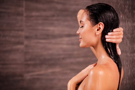 wet breast: Enjoying a shower. Side view of beautiful young shirtless woman taking shower  Stock Photo