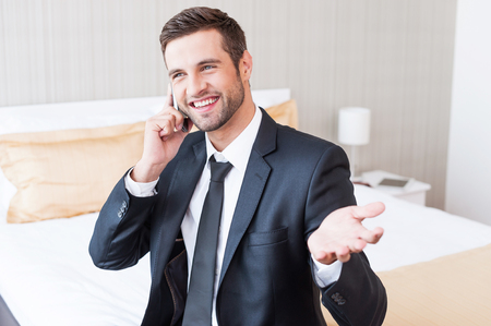 Good business talk. Happy young businessman in formalwear talking on the mobile phone and smiling while sitting on the bed in hotel room  photo