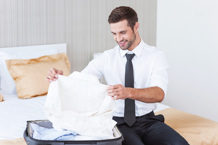 Choosing new shirt to wear. Handsome young man in shirt and tie unpacking his suitcase and smiling while sitting on the bed in hotel room  Stok Fotoğraf