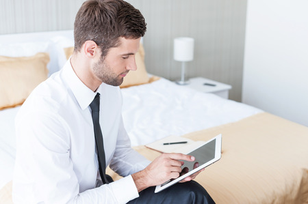 호텔 방에서 일하기. 자신감이 젊은 사업가 셔츠와 넥타이 호텔 방에서 침대에 앉아있는 동안 디지털 태블릿에서 작동 스톡 콘텐츠