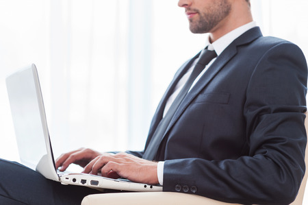 face side: Working on laptop. Side view of young businesswoman in suit working on laptop while sitting at the chair