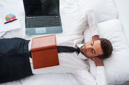 Businessman sleeping. Top view of handsome young man in shirt and tie holding hands behind head and keeping eyes closed while lying in bed at the hotel room  photo