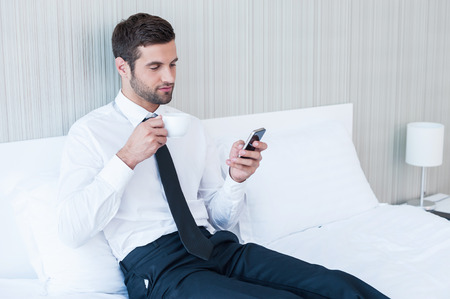 hotel worker: Typing business message. Confident young man in shirt and tie drinking coffee and holding mobile phone while lying in bed at the hotel room