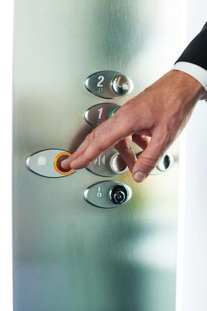 pushing the button: Man pushing button. Close-up of male hand pushing button of elevator Foto de archivo