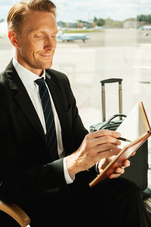 Businessman making notes. Side view of confident businessman in formalwear writing something in note pad while waiting for a flight in airport  photo
