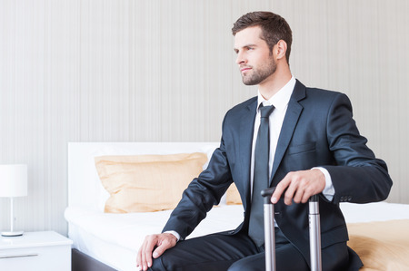 Ready to new business trip. Confident young businessman in formalwear carrying suitcase and smiling while sitting on the bed in hotel room  photo