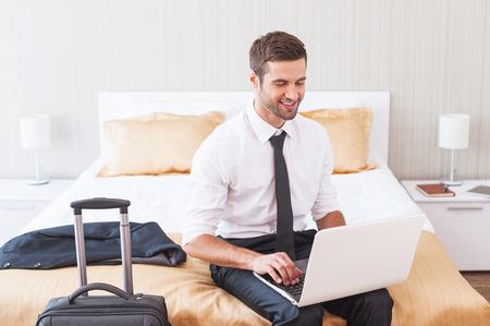 beau jeune homme: Rester en contact avec le bureau. Beau jeune homme en chemise et cravate travaillant sur ordinateur portable et souriant alors qu'il �tait assis sur le lit dans la chambre d'h�tel