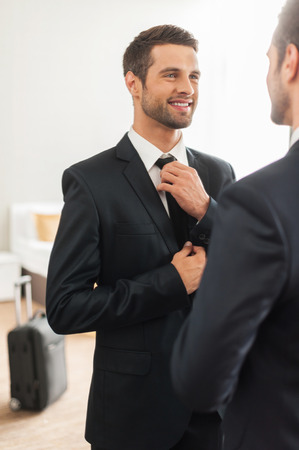 Used to look perfect. Handsome young man in formalwear adjusting his necktie and smiling while standing against mirror in hotel room Archivio Fotografico