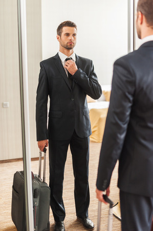 Ready for business trip. Confident young man in formalwear adjusting his necktie while standing against mirror in hotel room Stockfoto
