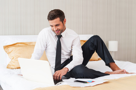 No time for rest. Handsome young man in shirt and tie working on laptop and smiling while sitting in bed at the hotel room  photo