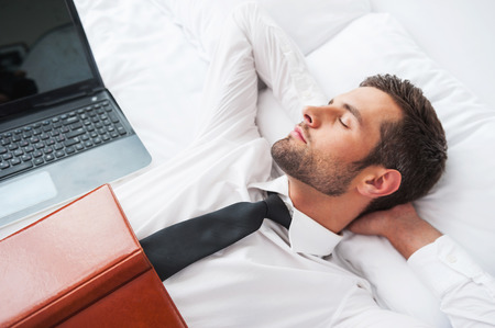 Tired of work. Top view of handsome young man in shirt and tie holding hands behind head and keeping eyes closed while lying in bed at the hotel room
