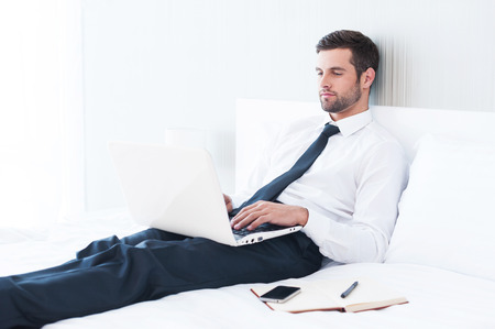 no time: No time to relax. Confident young man in shirt and tie working on laptop while lying in bed at the hotel room  Stock Photo