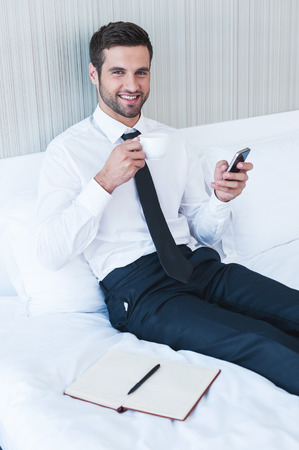 Typing business message. Cheerful young man in shirt and tie drinking coffee and holding mobile phone while lying in bed at the hotel room  photo