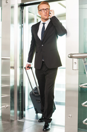 Executive on the go. Full length of confident young man in formalwear carrying suitcase and talking on the mobile phone while getting out of elevator photo