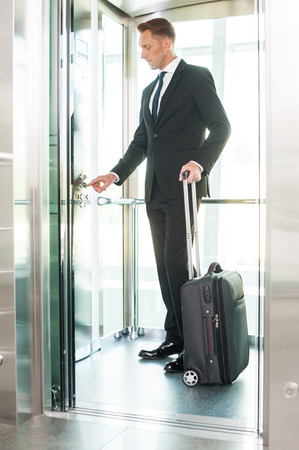 people in elevator: Businesswoman in elevator. Full length of confident young man in formalwear pushing button while standing inside of elevator Stock Photo