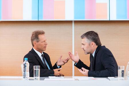 personas discutiendo: discusión caliente. Dos hombres de negocios furioso en discusiones Formal y gesticulando mientras se está sentado junto a la mesa con monitor de gran tamaño sobre ellos