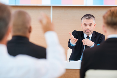 focus group: Yes, you! Confident mature man in formalwear giving a word to someone from audience while sitting in conference hall   Stock Photo