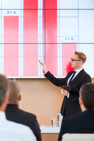 projection screen: Presentation in conference hall. Confident young man in formalwear pointing projection screen with graph on it while making presentation in conference hall with people on the foreground Stock Photo