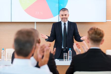 aplaudiendo: Celebrar el éxito. Hombre maduro confía en formalwear gesticula y que sonríe mientras que hace la presentación en sala de conferencias con la gente aplaudiendo en el primer plano