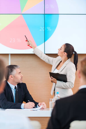 Discussing report. Confident young woman in formalwear pointing projection screen while making presentation in conference hall with people on foreground photo