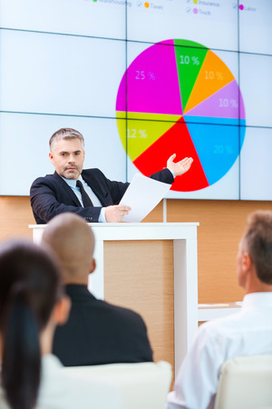 Public speaker. Confident grey hair man in formalwear pointing projection screen with graph on it while making presentation in conference hall with people on the foreground
