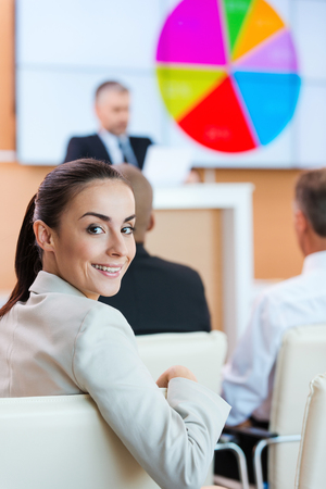 siting: Businesswoman at the conference. Confident young woman in formalwear looking over shoulder and smiling while sitting at the conference hall with public speaker in the background