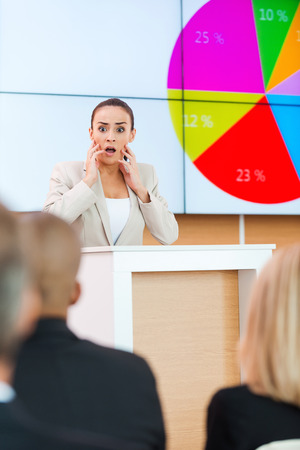 young fear: Fear of public speaker. Shocked young woman in formalwear touching her face with hands while standing at the tribune in conference hall with people on foreground