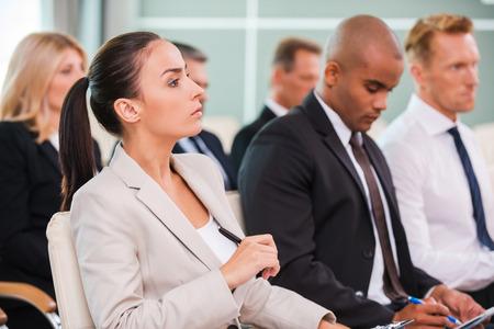 capacitacion: Conferencia de negocios. Grupo de hombres de negocios en ropa formal que se sientan en las sillas en sala de conferencias y escribiendo algo gin sus blocs de notas Foto de archivo