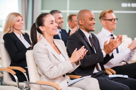 Applaudisseren om de luidspreker. Groep van gelukkige mensen uit het bedrijfsleven in formalwear zitten aan de stoelen in conferentiezaal en applaudisseren