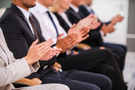 훌륭한 성공. 행에 앉아있는 동안 사업 사람들의 그룹은 손을 박수
