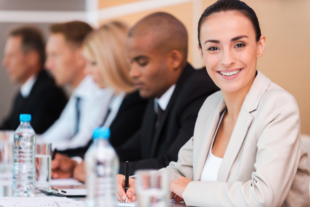 Confident business expert. Group of business people sitting\ in a row and writing something in their note pads while beautiful\ young woman in formalwear looking at camera and smiling