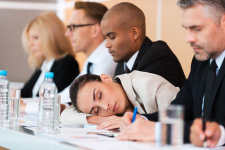 participant: Sleeping at the conference. Tired businesswoman sleeping while sitting at the table with her colleagues  Stock Photo