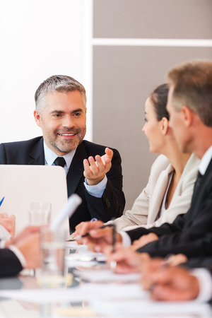 business relationship: Good news for our company! Business people in formalwear discussing something while sitting together at the table Stock Photo