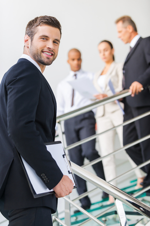 over the shoulder view: Young and successful. Low angle view of confident young man in formalwear looking over shoulder and smiling while moving up by staircase with people in the background  Stock Photo