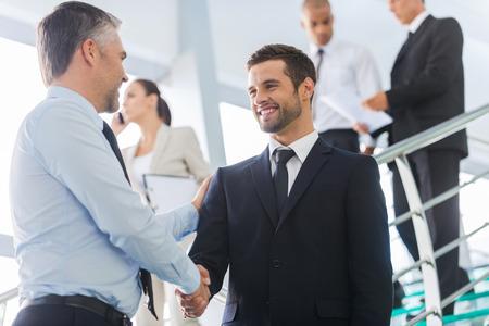 personnes: Les hommes d'affaires se serrant la main. Deux hommes d'affaires confiants serrant la main et souriant tout en se tenant à l'escalier avec des gens en arrière-plan