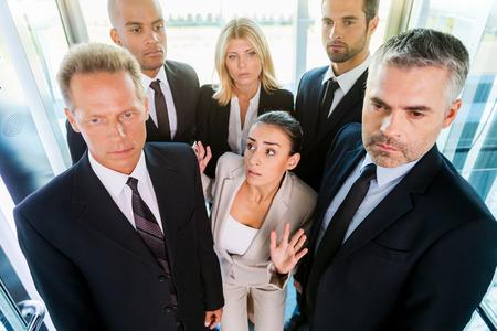 Ahogamiento en las personas. Vista superior de la mujer joven temerosa en formalwear sentirse atrapado por la multitud mientras está de pie en el ascensor Foto de archivo - 31386288