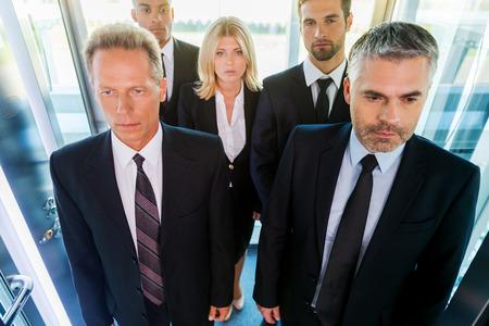 Mensen in de lift. Bovenaanzicht van mensen uit het bedrijfsleven in formalwear staande in de lift Stockfoto