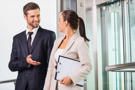 Discussing project with colleague. Two cheerful business people discussing something and smiling while getting out from elevator