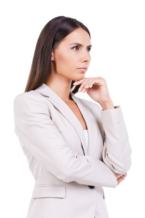 only one young woman: Looking for inspiration. Thoughtful young businesswoman in suit holding hand on chin and looking away while standing against white background
