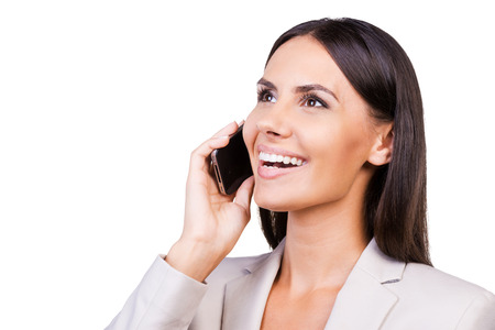 Good talk. Confident young businesswoman in suit talking on the mobile phone and smiling while standing isolated on white background photo