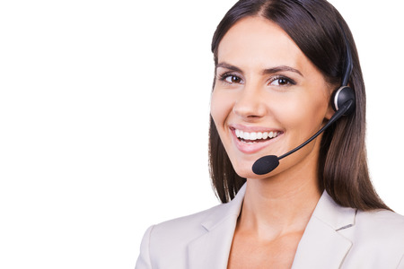 executive women: Confident female operator. Beautiful young businesswoman in headset smiling while isolated on white background Stock Photo