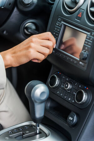 Examining her new car. Close-up of woman in formalwear touching dashboard with finger while sitting in car  photo